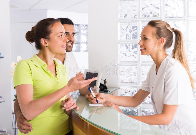 Par med receptionisten på kliniken royaltyfria bilder