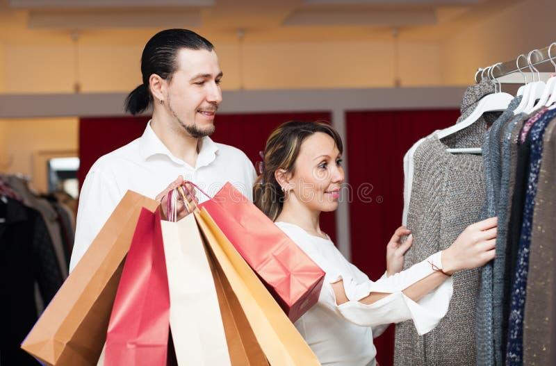 Par med shoppingpåsar som väljer kläder arkivfoton