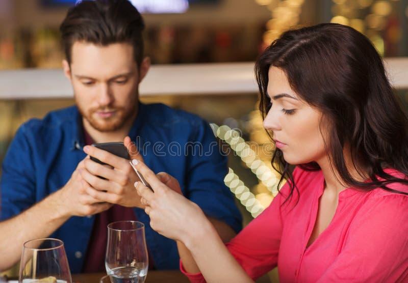 Par med smartphones som äter middag på restaurangen royaltyfri foto