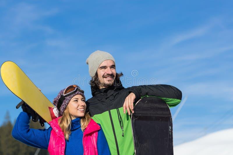 Par med snowboarden Ski Resort Snow Winter Mountain som ler extrem sportsemester för man och för kvinna royaltyfri fotografi