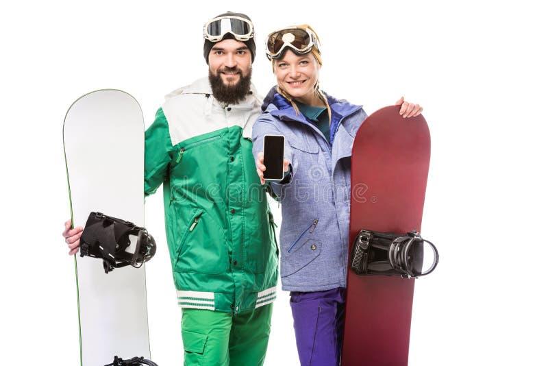 Par med snowboards som visar smartphonen royaltyfria bilder