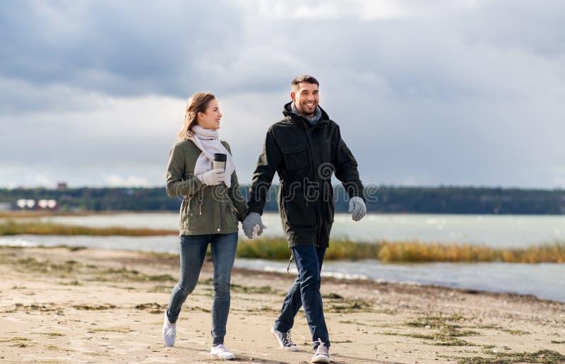 Par med torktumlaren som promenerar höststranden arkivfoto