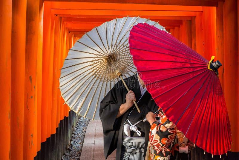 Par med traditionella japanska paraplyer som poserar p? toriiportar i Kyoto royaltyfri bild