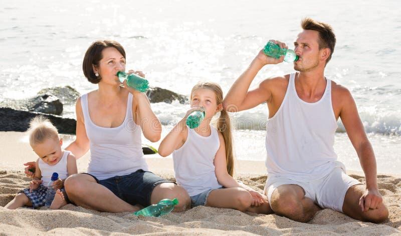 Par med två ungar som dricker sötvatten på den sandiga stranden arkivbild