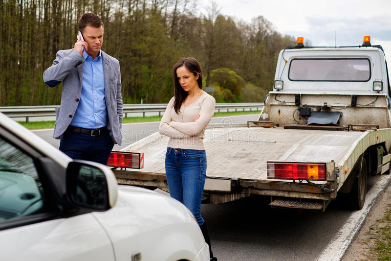 Par near den brutna bilen på en vägren royaltyfri bild