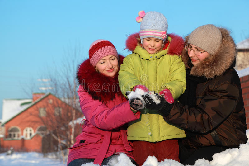 Par offer to daughter to make snowball outdoors royalty free stock photos