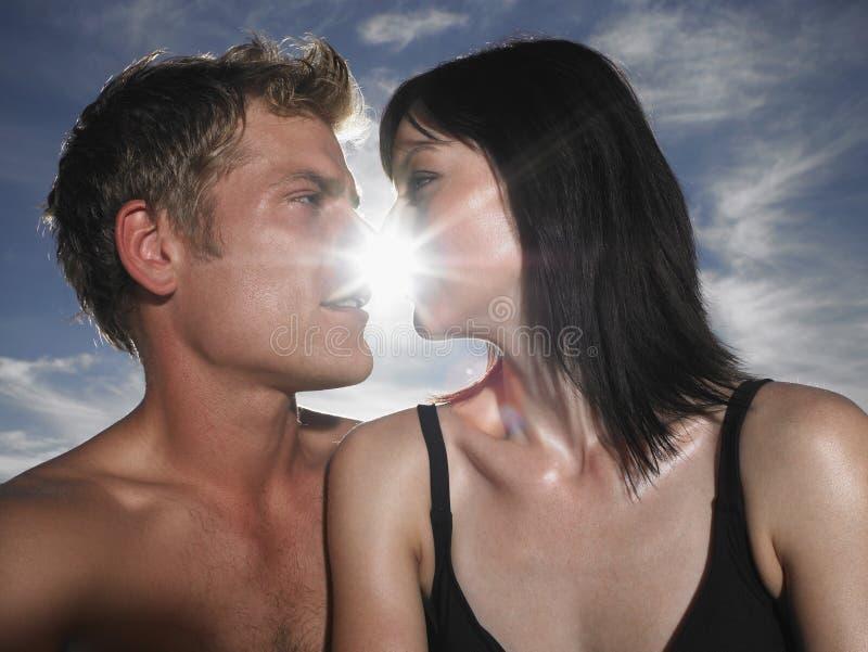 Par omkring som ska kyssas med solen bakom royaltyfri fotografi