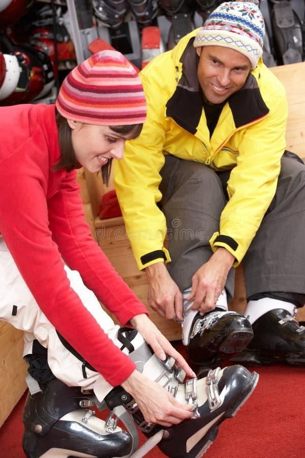 Par på att försöka på skidar kängor i hyra shoppar fotografering för bildbyråer