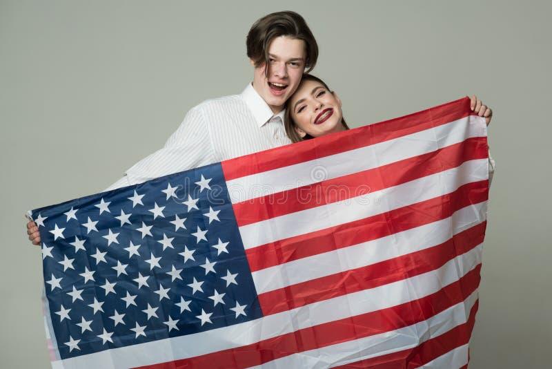 Par på att le framsidahållflaggan av USA Grabb och flicka som är lyckliga med amerikanska flaggan, grå bakgrund utomlands löpa royaltyfri foto