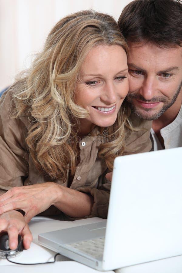 Par på bärbara datorn. arkivbild