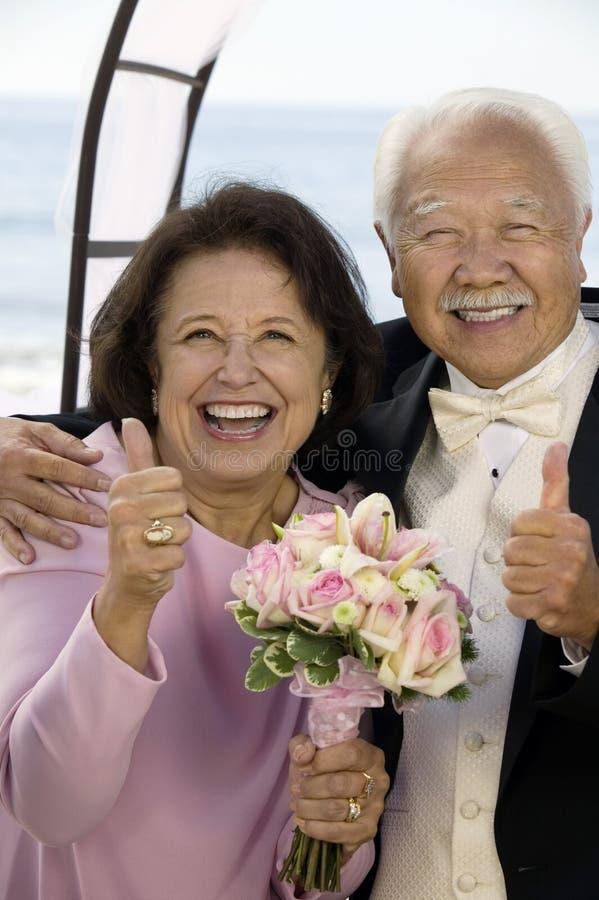 Par på bröllop som ger att le för tummar-upp (ståenden) arkivbilder