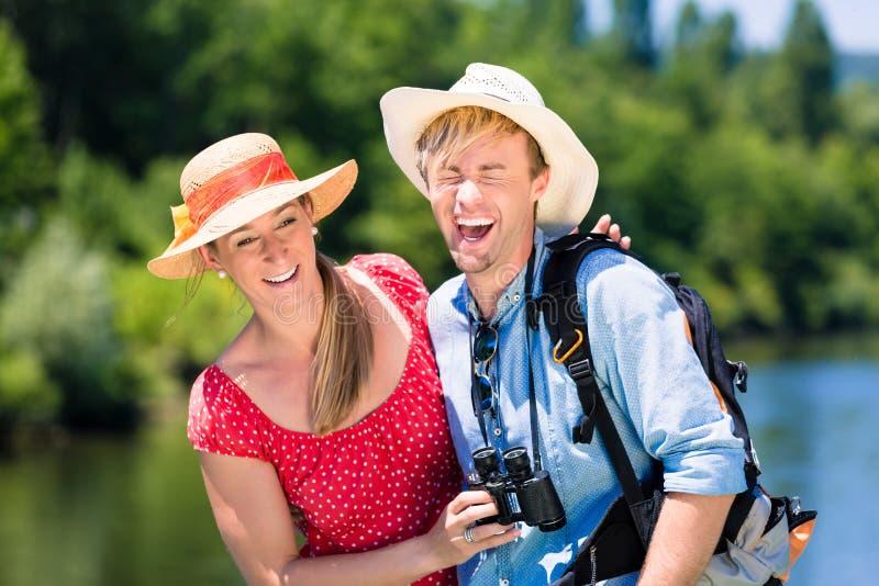 Par på floden kryssar omkring bärande solhattar i sommar royaltyfria foton