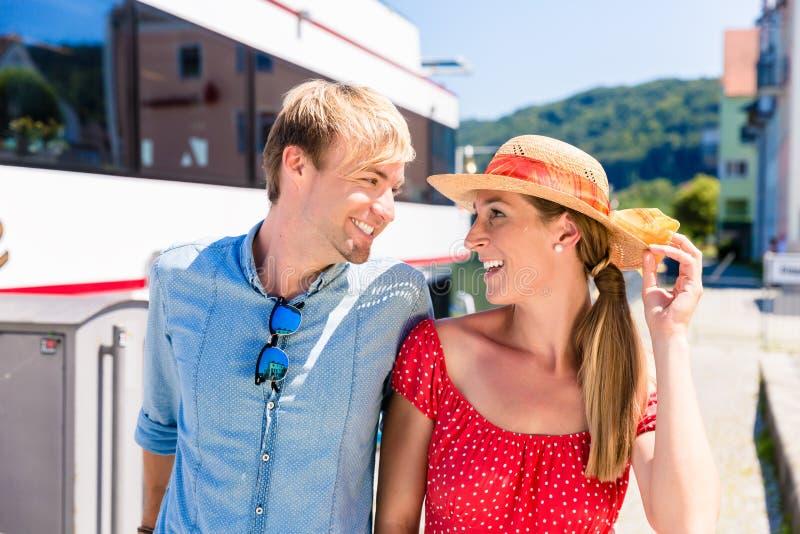 Par på floden kryssar omkring i bärande solhattar för sommar royaltyfri foto
