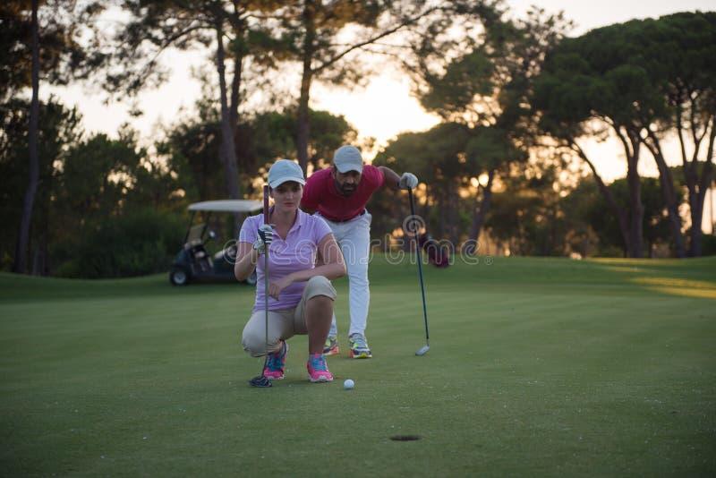 Par på golfbana på solnedgången arkivfoto
