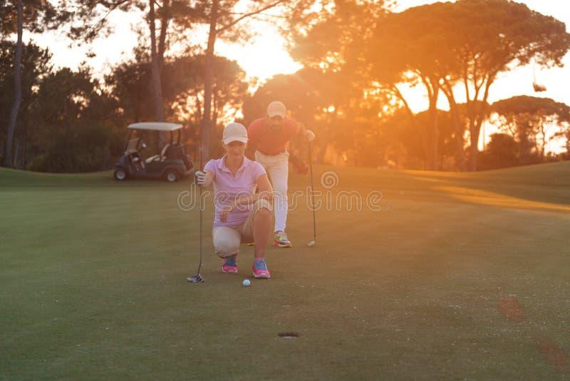 Par på golfbana på solnedgången royaltyfri bild
