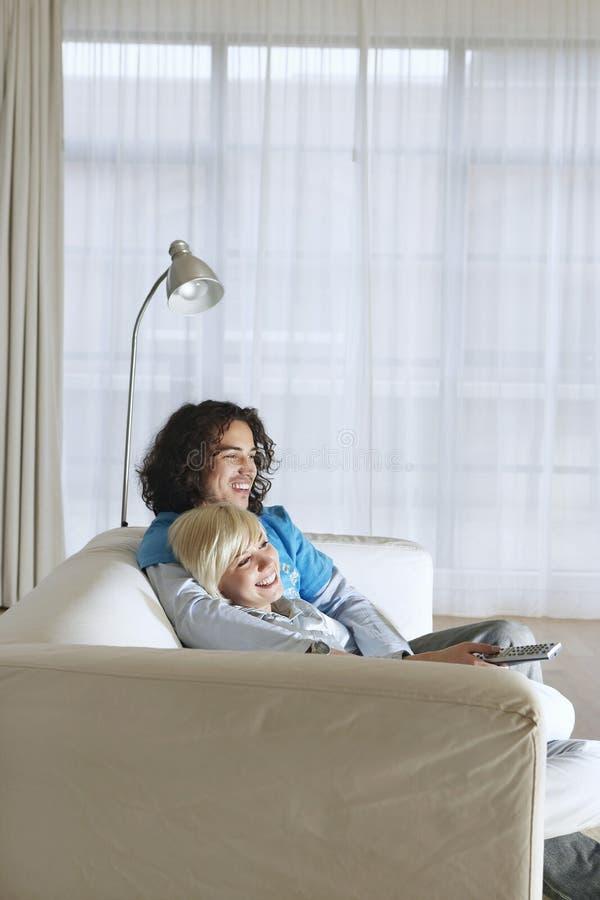 Par på hållande ögonen på TV för soffa arkivfoto