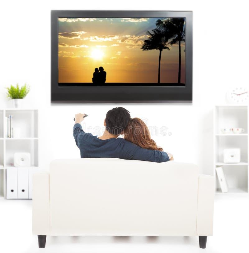 Par på hållande ögonen på TV för soffa med fjärrkontroll fotografering för bildbyråer