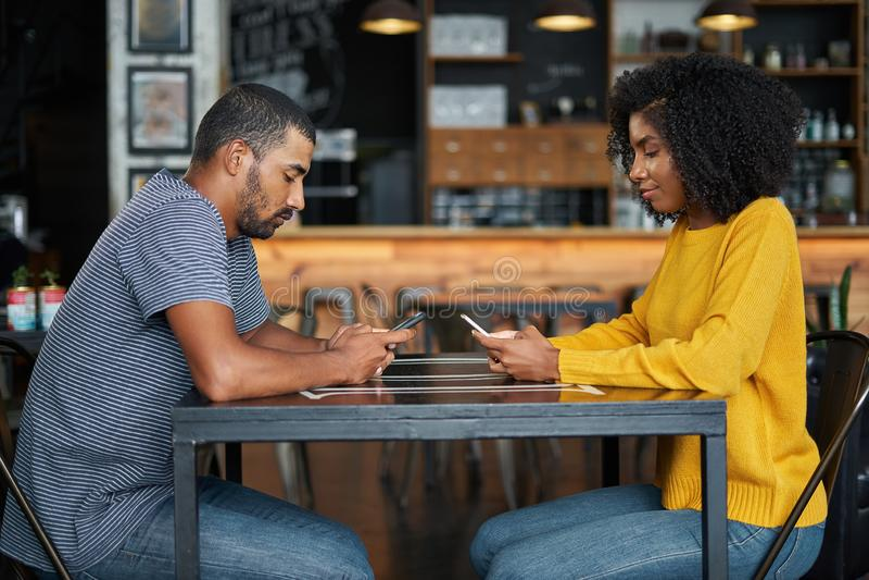 Par på kafétabellen genom att använda mobiltelefoner royaltyfria foton