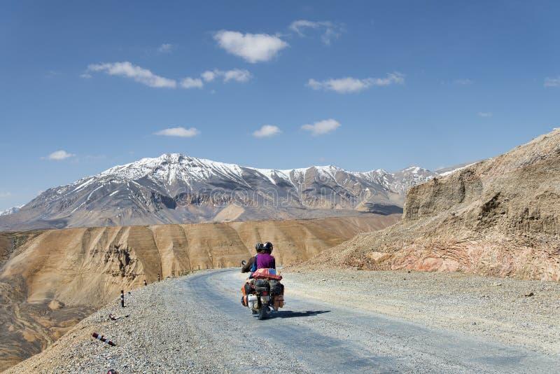 Par på mopedridning bland berg royaltyfria foton