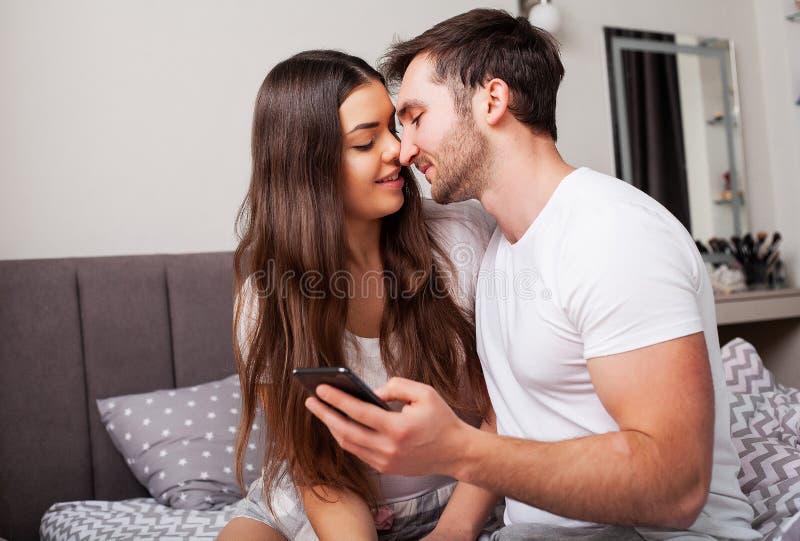 Par på säng som ser smartphonen och att le royaltyfri foto