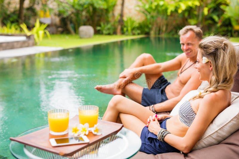 Par på semestern som kopplar av vid pölen royaltyfri fotografi