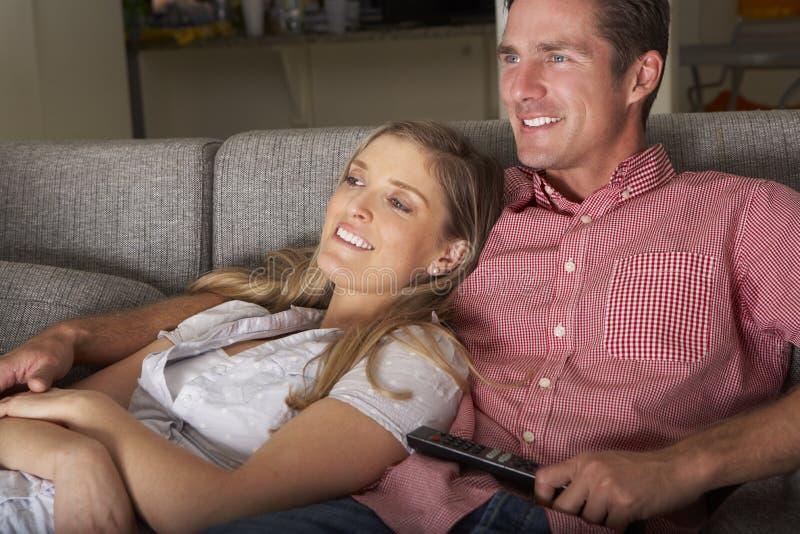 Par på Sofa Watching TV tillsammans royaltyfria bilder
