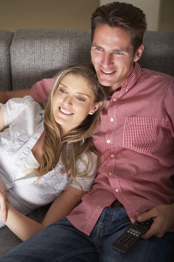 Par på Sofa Watching TV tillsammans fotografering för bildbyråer