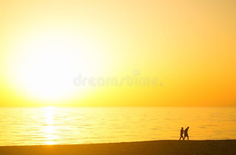 Par på solnedgången på stranden arkivbilder