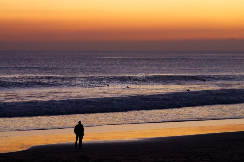 Par på stranden av hållande ögonen på surfare för skymning royaltyfri bild