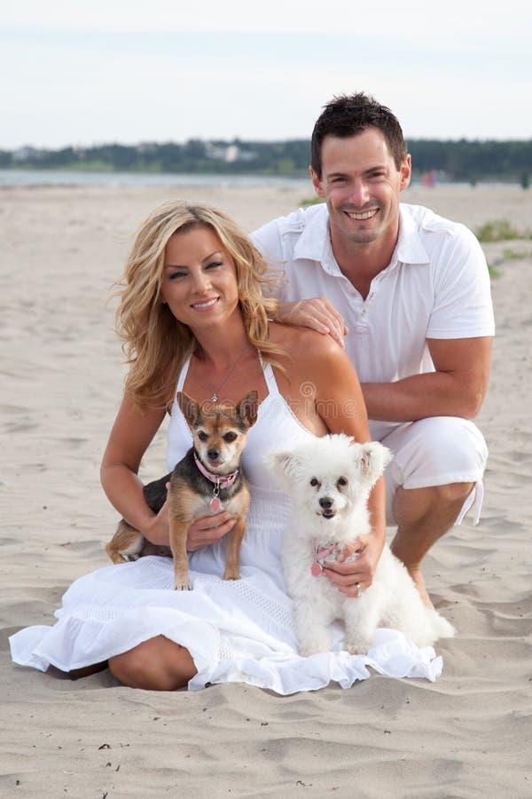 Par på stranden med älsklings- hundkapplöpning royaltyfria bilder