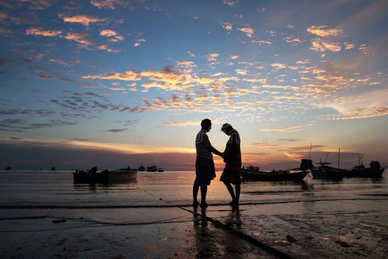 Par på strandsolnedgångbakgrunden royaltyfri foto