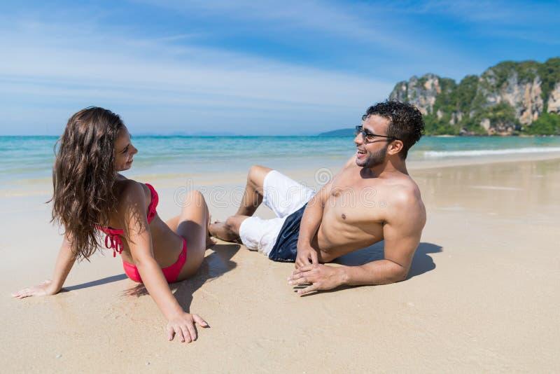 Par på strandsommarsemester, ungdomarsom sitter på sand, hav för mankvinnahav arkivfoton