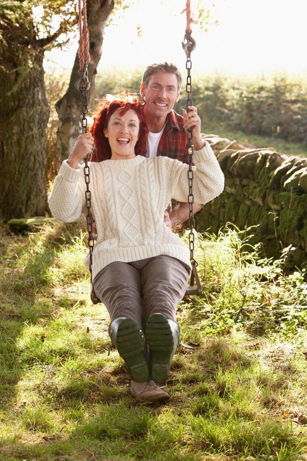 Par på swing i landsträdgård royaltyfria bilder