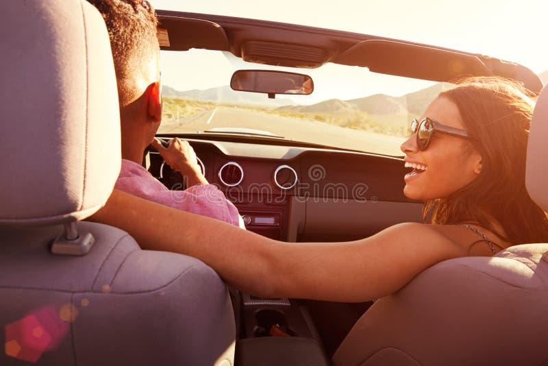 Par på vägturen som kör i konvertibel bil arkivfoton