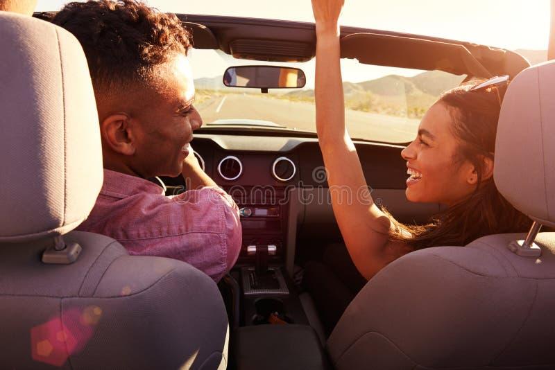 Par på vägturen som kör i konvertibel bil royaltyfria bilder