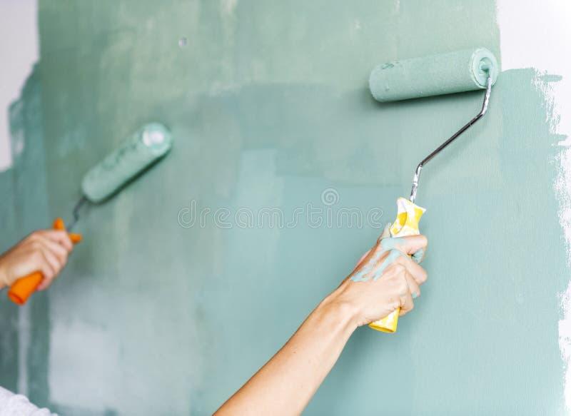 Par renoverar, genom att måla huset arkivfoto