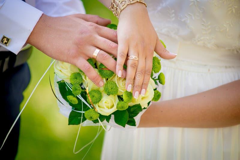 Par satte deras händer på en brud- bukett royaltyfri fotografi