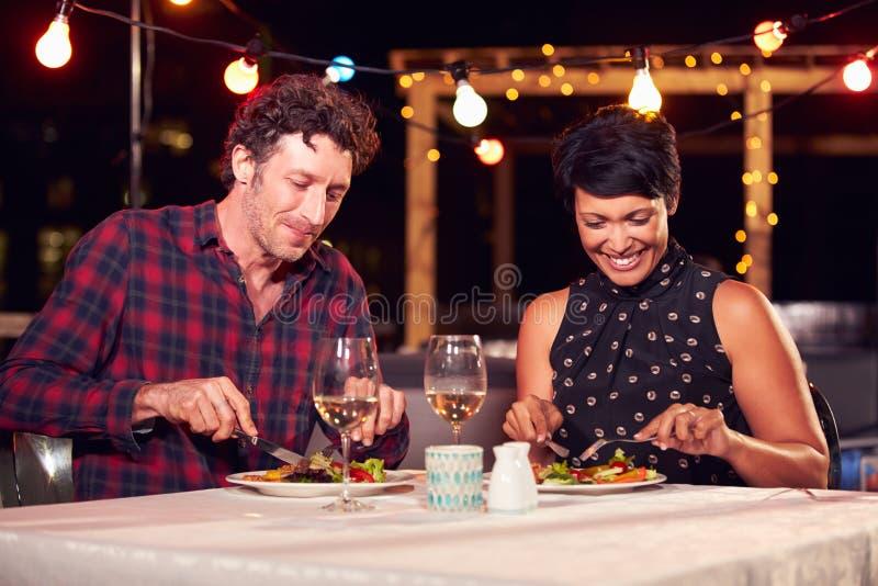 Par som äter matställen på takrestaurangen royaltyfria foton