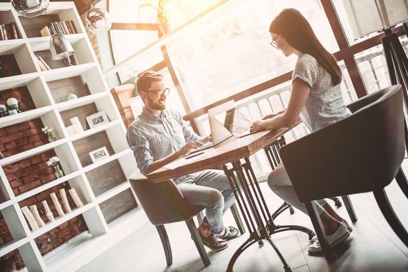 Par som arbetar i kafé royaltyfri fotografi
