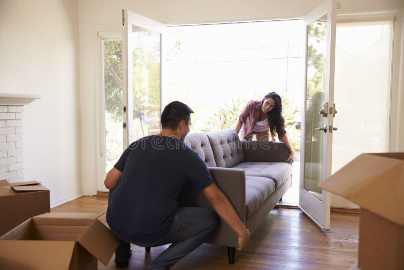 Par som bär Sofa Into New Home On den rörande dagen royaltyfri bild