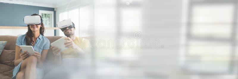 Par som bär VR-hörlurar med mikrofon vid fönster arkivfoto