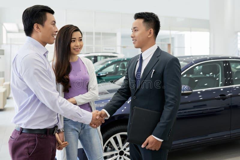 Par som besöker bilåterförsäljaren fotografering för bildbyråer