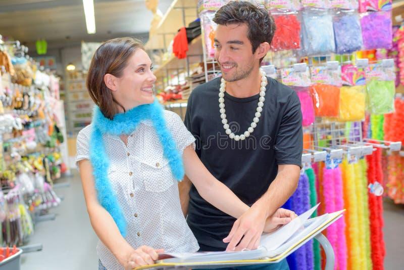 Par som bläddrar katalogmaskeradkläderdräkter royaltyfria foton
