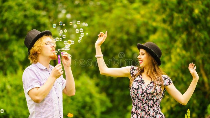 Par som blåser utomhus- bubblor arkivfoton