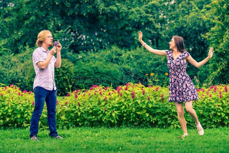 Par som bl?ser utomhus- bubblor royaltyfri fotografi