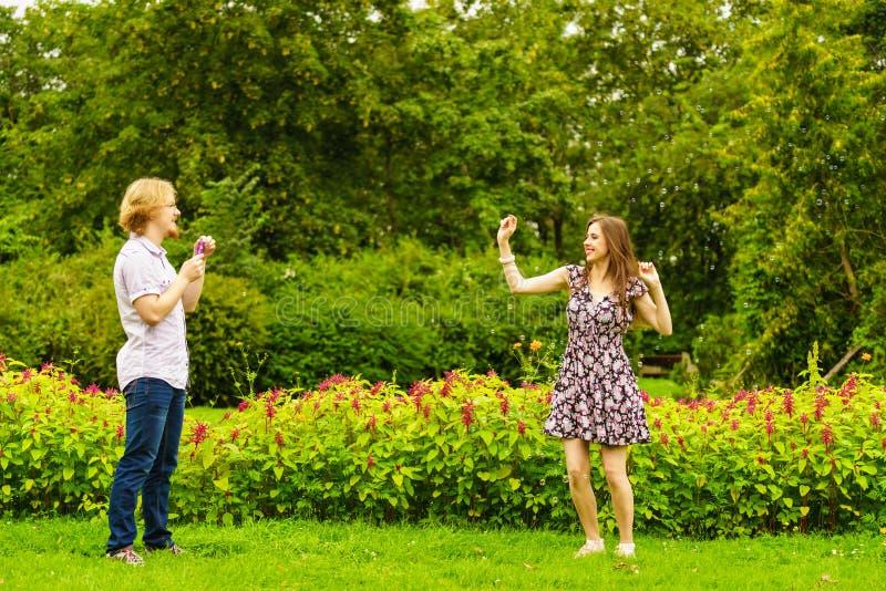Par som bl?ser utomhus- bubblor arkivfoton