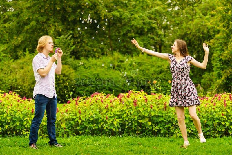 Par som bl?ser utomhus- bubblor fotografering för bildbyråer