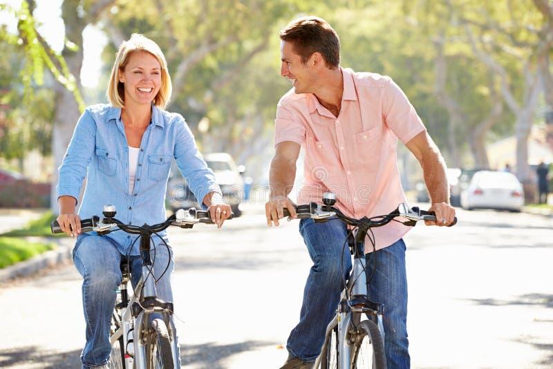 Par som cyklar på den förorts- gatan royaltyfri bild