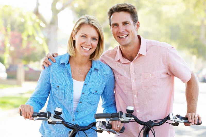 Par som cyklar på den förorts- gatan royaltyfri foto