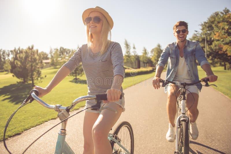 Par som in cyklar, parkerar royaltyfria bilder
